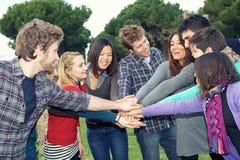 Étudiants multiraciaux avec des mains sur la pile photo stock