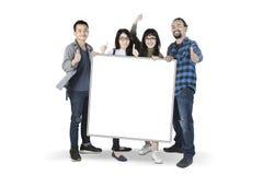 Étudiants multiraciaux avec le conseil vide Image libre de droits
