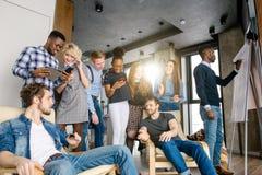 Étudiants noirs intelligents faisant le travail pour ses amis tandis qu'ils se reposent de retour Photographie stock libre de droits