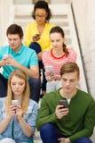 Étudiants occupés avec des smartphones se reposant sur des escaliers Photographie stock