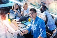 Étudiants optimistes faisant le selfie dans le café Photographie stock libre de droits