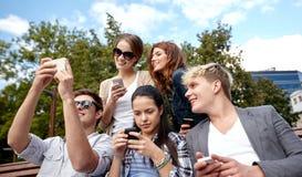 Étudiants ou adolescents avec des smartphones au campus Images stock