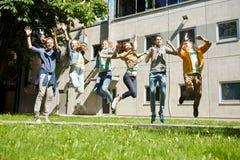 Étudiants ou amis adolescents heureux sautant dehors Photos libres de droits