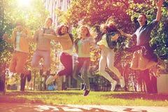 Étudiants ou amis adolescents heureux sautant dehors Image libre de droits