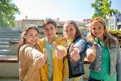 Étudiants ou amis heureux montrant des pouces  Photographie stock libre de droits