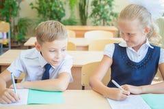 Étudiants ou camarades de classe dans la salle de classe d'école se reposant ensemble au bureau Images libres de droits