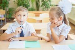 Étudiants ou camarades de classe dans la salle de classe d'école se reposant ensemble au bureau Photo stock