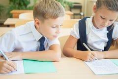 Étudiants ou camarades de classe dans la salle de classe d'école se reposant ensemble au bureau Photos libres de droits