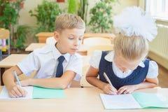 Étudiants ou camarades de classe dans la salle de classe d'école se reposant ensemble au bureau Images stock