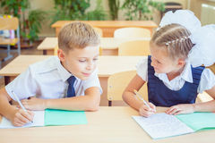 Étudiants ou camarades de classe dans la salle de classe d'école se reposant ensemble au bureau Image libre de droits