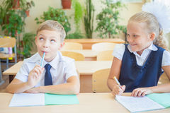 Étudiants ou camarades de classe dans la salle de classe d'école se reposant ensemble au bureau Image stock