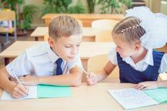 Étudiants ou camarades de classe dans la salle de classe d'école se reposant ensemble au bureau Photos stock