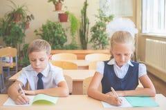 Étudiants ou camarades de classe dans la salle de classe d'école se reposant ensemble au bureau Photographie stock libre de droits