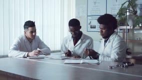 Étudiants ou médecins de diversité travaillant avec le comprimé clips vidéos