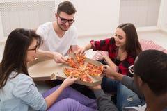Étudiants partageant la partie de pizza à la maison Image libre de droits