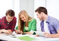 Étudiants passant en revue dans le PC de comprimé à l'école Image stock
