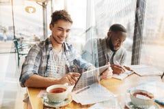 Étudiants positifs ayant l'amusement dans le café Images libres de droits