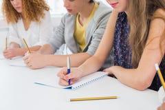 Étudiants prenant des notes dans la classe Images stock