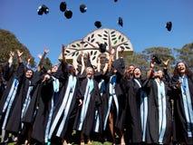 Étudiants projetant des chapeaux de graduation Image libre de droits