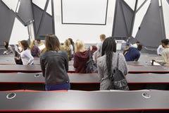 Étudiants quittant le théâtre de conférence d'université, vue arrière images stock