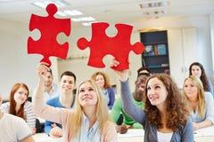Étudiants résolvant le puzzle denteux en équipe Images stock