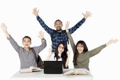 Étudiants réussis avec un ordinateur portable et des manuels Image libre de droits