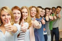 Étudiants réussis retenant des pouces Photographie stock libre de droits