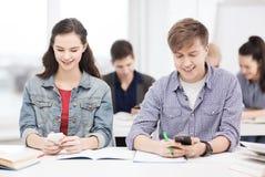 Étudiants regardant dans le smartphone l'école Photo libre de droits