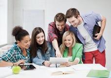 Étudiants regardant le PC de comprimé l'école Photos stock