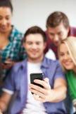 Étudiants regardant le smartphone l'école Image libre de droits