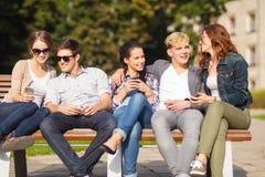 Étudiants regardant les smartphones et le PC de comprimé Photographie stock