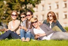 Étudiants regardant les smartphones et le PC de comprimé Photos libres de droits