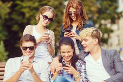 Étudiants regardant les smartphones et le PC de comprimé Photo libre de droits