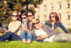 Étudiants regardant les smartphones et le PC de comprimé Photographie stock libre de droits