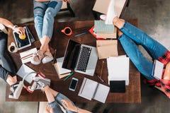 Étudiants s'asseyant à la table avec des livres et des dispositifs numériques Photographie stock libre de droits