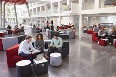 Étudiants s'asseyant dans l'oreillette d'université, trois dans le premier plan Photographie stock