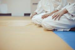 Étudiants s'asseyant dans un kimono dans le gymnase image stock