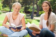 Étudiants s'asseyant en parc avec leurs livres Photographie stock libre de droits