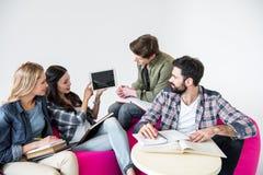 Étudiants s'asseyant sur des chaises de sac à haricots et étudiant avec le comprimé numérique dans le studio Photo libre de droits