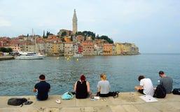 Étudiants s'asseyant sur le quai dessinant la vieille ville de Rovinj Images stock
