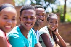 étudiants s'asseyants extérieurs d'université de campus de banc Photos libres de droits