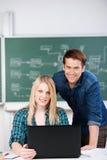 Étudiants sûrs avec l'ordinateur portable au bureau Photographie stock libre de droits