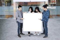 Étudiants se dirigeant sur le conseil blanc avec l'espace de copie Photos stock
