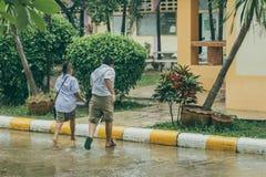 Étudiants se précipitant pour traverser la rue sous la pluie avant maison arrière image libre de droits