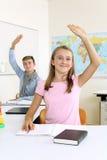 Étudiants soulevant leurs mains dans la classe Images stock