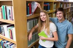 Étudiants souriant à l'appareil-photo dans la bibliothèque Photo stock