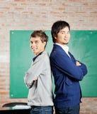 Étudiants tenant des bras croisés dans la salle de classe Photo stock