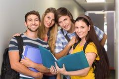Étudiants tenant des dossiers au couloir d'université Images libres de droits