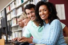 Étudiants travaillant sur des ordinateurs dans la bibliothèque Images stock
