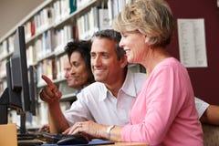 Étudiants travaillant sur des ordinateurs dans la bibliothèque Photos libres de droits
